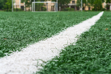 Artificially turfed football field with green grass and white line, close-up view