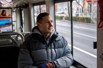 White male passenger sitting on the bus looking out the window
