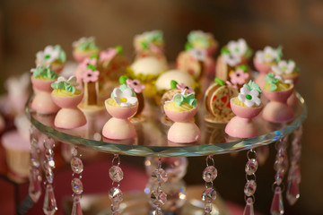 Delicious dessert variety of playful or themed bite-sized cakes shaped as small white and pink chocolate cups with icing sugar flowers, displayed on an embellished crystal cake stand