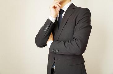 考えるスーツのビジネスマン男性