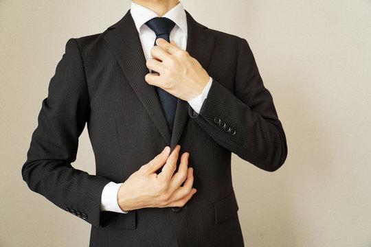 スーツのビジネスマン ネクタイを締める