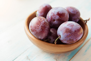 Fresh plums in wooden bowl on table
