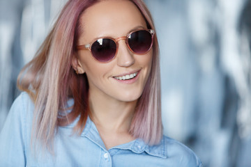 Close-up portrait of a charming hipster student in sunglasses with pink hair in a jersey shirt. Cute young girl in stylish modern clothes posing in studio