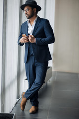 stylish Indian bisinessman is standing near the window.full length photo. rest, free time. leisure time. beauty
