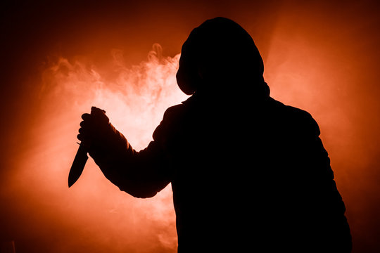 A dangerous hooded man standing in the dark and holding a knife. Face can not be seen. Committing a crime concept. Selective focus
