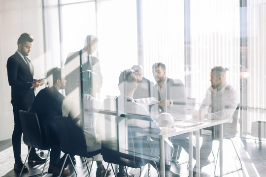 Side view of blurred silhouettes of businessmen talking in conference room, view through the transparent glass wall