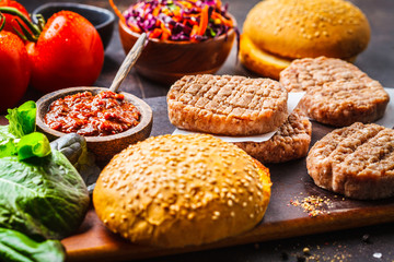 Ingredients for burgers on dark background, top view.