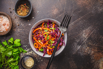 Coleslaw in a gray bowl on dark background. Red cabbage and carrot salad.