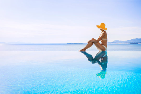 Young woman enjoying a sun in the luxury infinity pool. Enjoying life. Vacations, holidays and summer fun concept