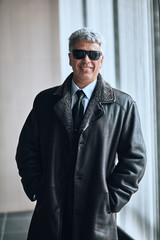 cheerful handsome man in sunglasses and leather jacket indoors. positive man in fashion stylish clothes looking at the camera