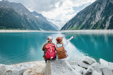 Travelers couple look at the mountain lake. Travel and active life concept with team. Adventure and travel in the mountains region in the Austria. Travel - image Fototapete