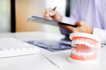 dentist with tooth model in dental office or clinic