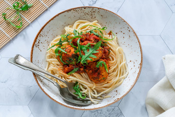 Spaghetti with tuna balls in spicy tomato sauce and rocket