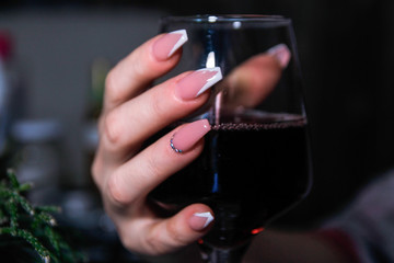 Woman's hands holding glass of wine. Nail art on hers nails.