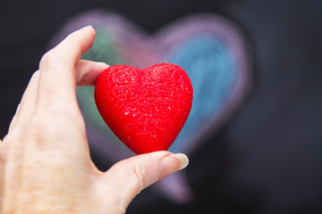 hand holding red heart with chalkboard background with drawings