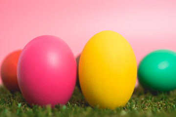 Colorful Easter eggs clean on grass and pink background