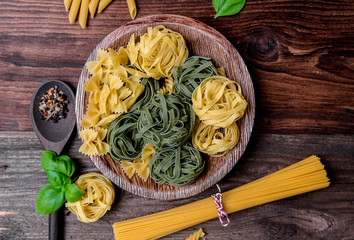 Assortment of many different raw pasta on a rustic board, beautifully arranged with basil and tomatoes