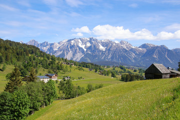 Panorama landscape and mountain meadows in Styria with view to the Dachstein mountains. View from Schladming, Austria
