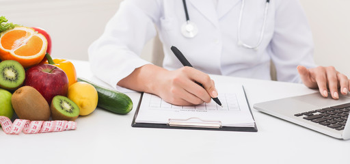 Doctor working with laptop and writing on paperwork