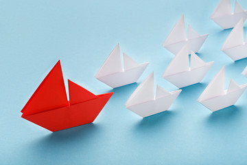 Red paper boat leading white ships, panorama