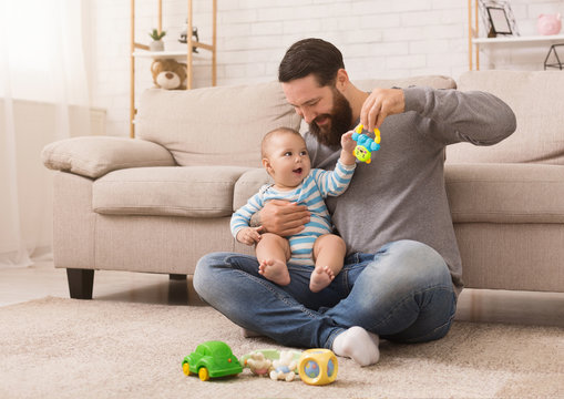 Happy father playing with his baby son with bright rattle