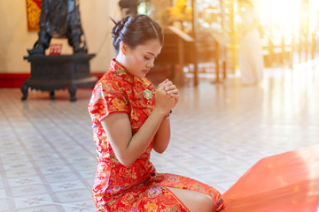 Happy Chinese new year. Asian woman in chinese dress traditional cheongsam and pray for the blessings of the temple.