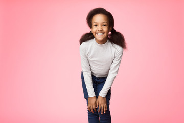 Pretty african-american girl posing over studio background