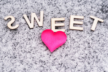 Valentine's Day. Heart of pink in the snow with the letters sweet. Valentine's Day. Soft focus. Background. Close-up.Heart drawn in the snow.