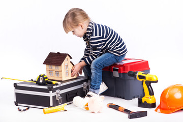 Little girl builder sitting on a construction suitcase.