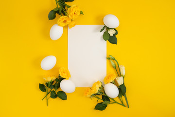 Empty card with easter decorations on yellow background with copy space.