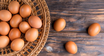 chicken eggs in a straw tray on an old wooden table