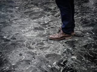 Low section of man wearing smart leather shoes standing on marble floor indoors.