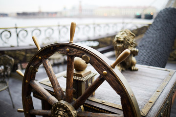 Wooden helm or sailing wheel with decorative ornaments on large ship floating upon river in urban environment
