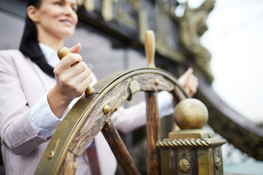 Hand of young successful businesswoman turning sailing wheel while leading large ship
