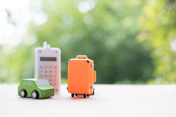 Miniature toy car and miniature orange suitcases with calculator