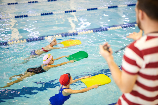 Group of little girls learning to swim with boards while swimming instructor training them