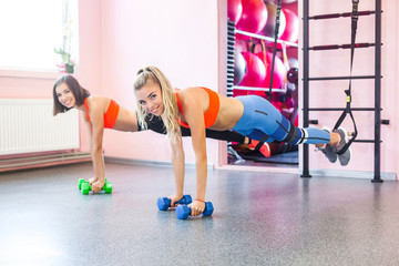 Young sporty women working out at trx loops