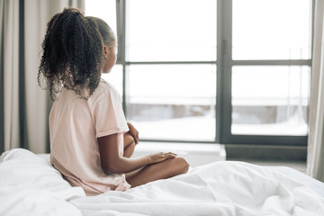 sad lonely girl sitting on the bed and looking at the window. back view photo. copy space. waitness. girl is waiting somebody in the morning. new day girl woke up in the morning