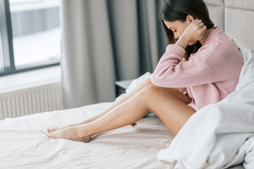 Depressed good looking girl sitting on bed at home. side view photo. depression, loneliness