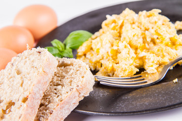 Scrambled eggs, some fresh eggs and wholemeal bread, and a fork, decorated with basil, on a white background