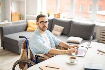 Young casual businessman in wheelchair looking at you while sitting by desk in front of laptop and networking