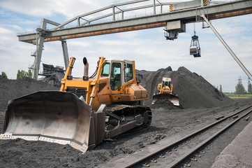 caterpillar tractor and travelling crane load black coal on supply field of thermoelectric power station