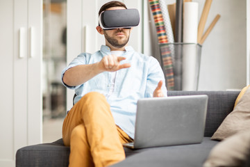 Young businessman with vr headset pointing at virtual display or pressing button while sitting in front of laptop