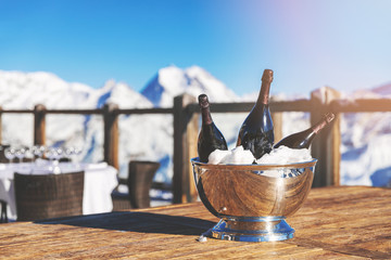 bucket with champagne bottles on restaurant table against snowy mountain background