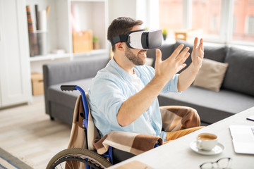 Cheerful young casual businessman in vr goggle keeping his hands in front of himself while looking at something virtual