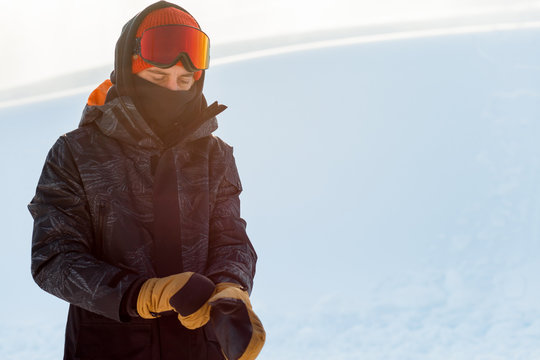 Young snowboarder in sportswear putting on his gloves before snowboarding. copy space. rest. free time. preparation