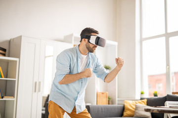 Young casual man with vr headset keeping his arms in front of himself while fighting with virtual rival in room