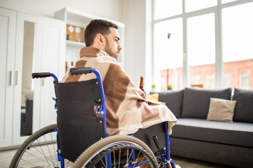 Young unhappy handicapped man in wheelchair wrapped in plaid having alcohol while spending time at home