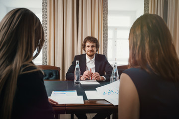 boss and employees/ Head talks to two subordinate girls about working in a business in a solid office