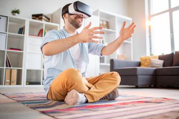 Happy young casual man with vr headset holding virtual stuff in hands while interacting in virtual reality
